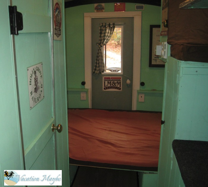Caboose Camper with seats folded down to make queen size bed.