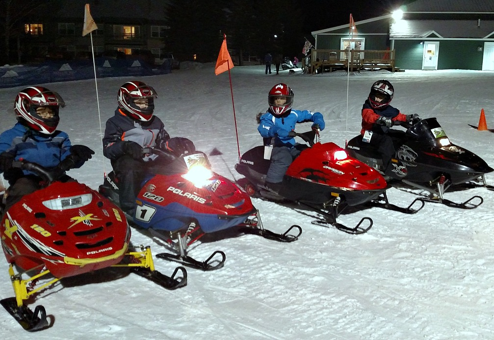 Kids riding mini snowmobiles at Smugglers Notch